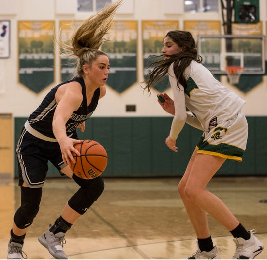 Manasquan's Faith Masonius tries to get by Red Bank Catholic's Justin Pissott. Manasquan vs Red Bank Catholic girls basketball.          