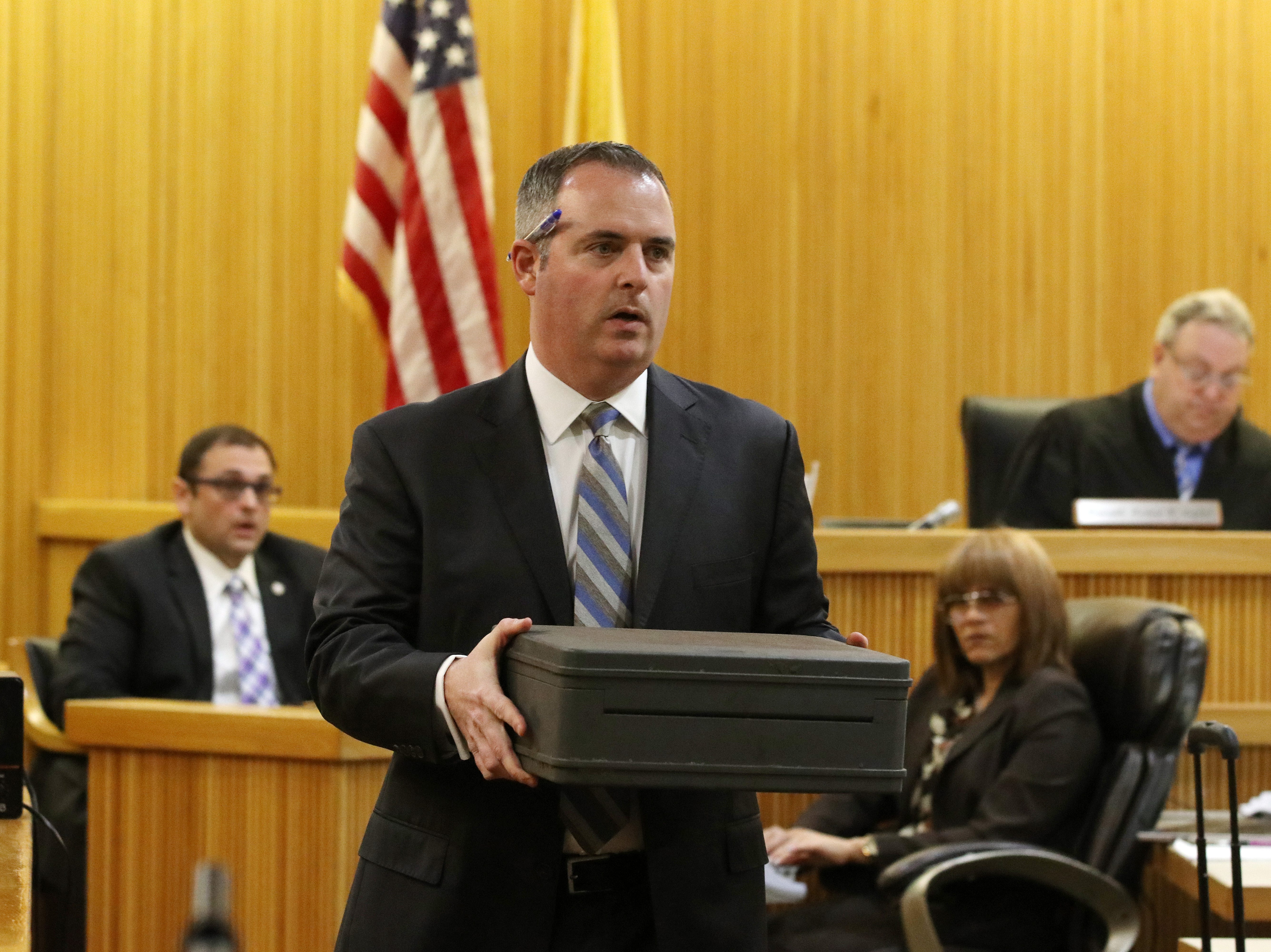 Christopher Decker, assistant Monmouth County prosecutor, carries Sarah Stern's safe which was found in Shark River Park, as he questions Detective Nicholas Cattelona of the Monmouth County Prosecutor's Office, during the trial of Liam McAtasney, who is charged with the murder of former high school classmate, Sarah Stern, before Superior Court Judge Richard W. English at the Monmouth County Courthouse in Freehold, NJ Wednesday, February 6, 2019.