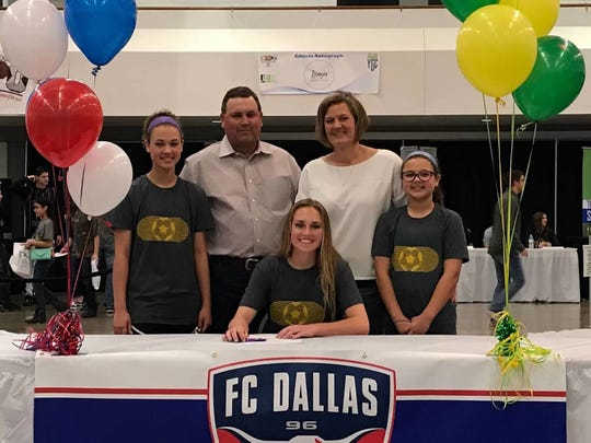 Wylie senior Jacqueline Williams, middle, is surrounded by family as she signs her National Letter of Intent to play soccer at Missouri Southern State University.