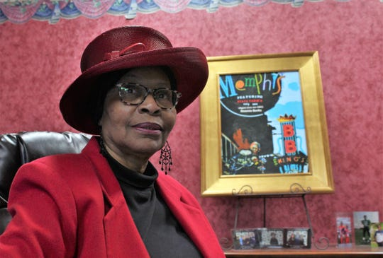 Neomia Banks at her desk, with a souvenir from an annual meeting held in Memphis - a framed image of B.B. King's nightspot personalized with her name.