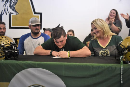 Abilene High offensive lineman Stevie Sifuentes, middle, signs his Letter of Intent to play at Colorado State University. Sifuentes was one of three Eagles to commit during a ceremony on Wednesday.