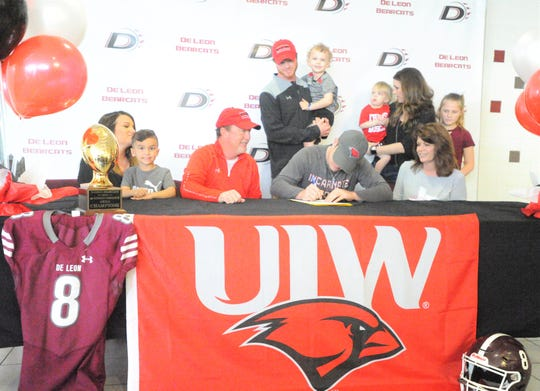 Surrounded by family, De Leon quarterback Kevin Yeager, center, signs his National Letter of Intent with the University of Incarnate Word at a ceremony Wednesday, Feb. 6, 2019, at De Leon High School.
