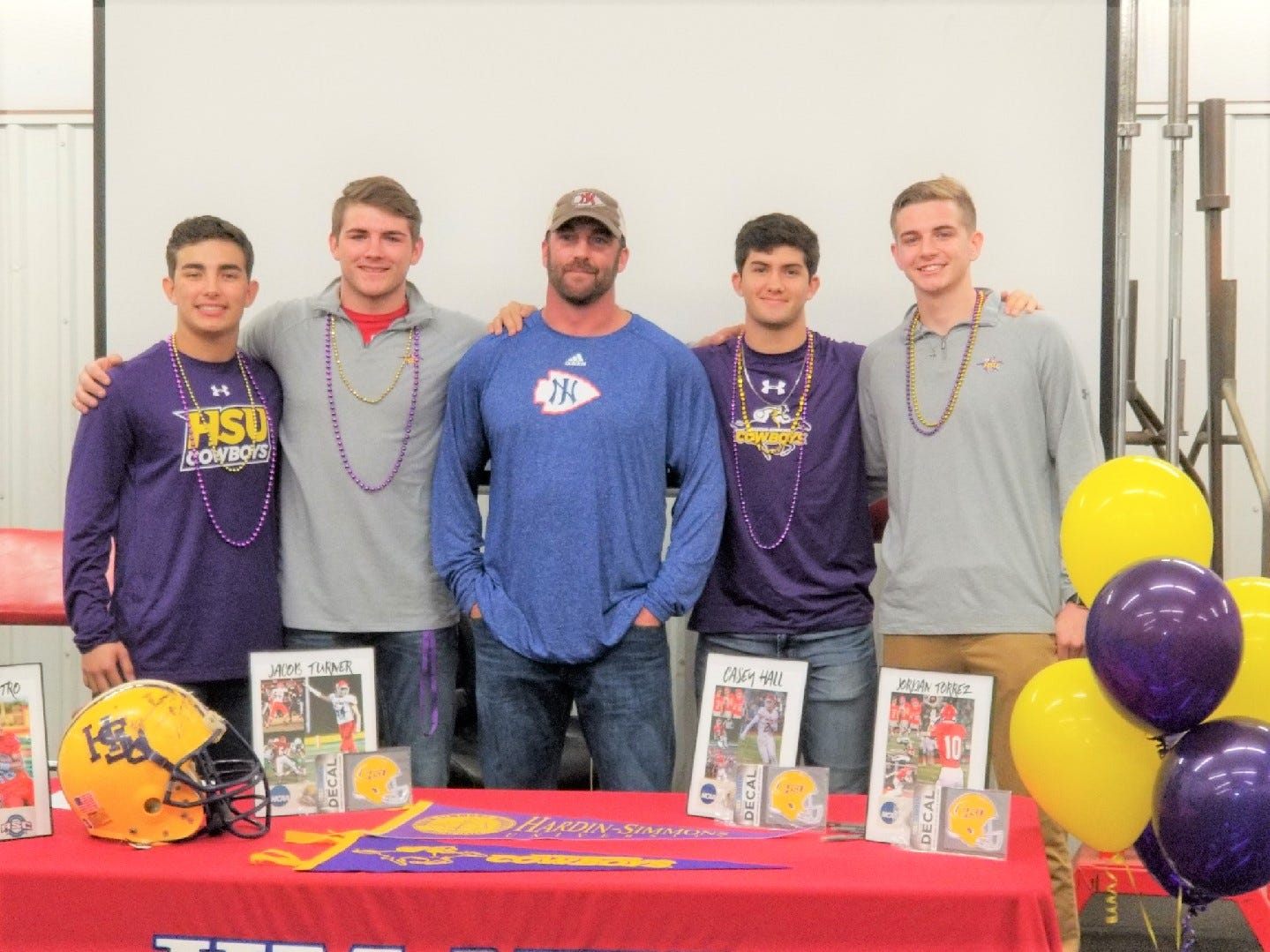 Jim Ned football coach Matt Fanning, center, joins seniors Cooper Castro, from left, Jacob Turner, Casey Hall and Jordan Torrez, who are headed to play football at Hardin-Simmons.