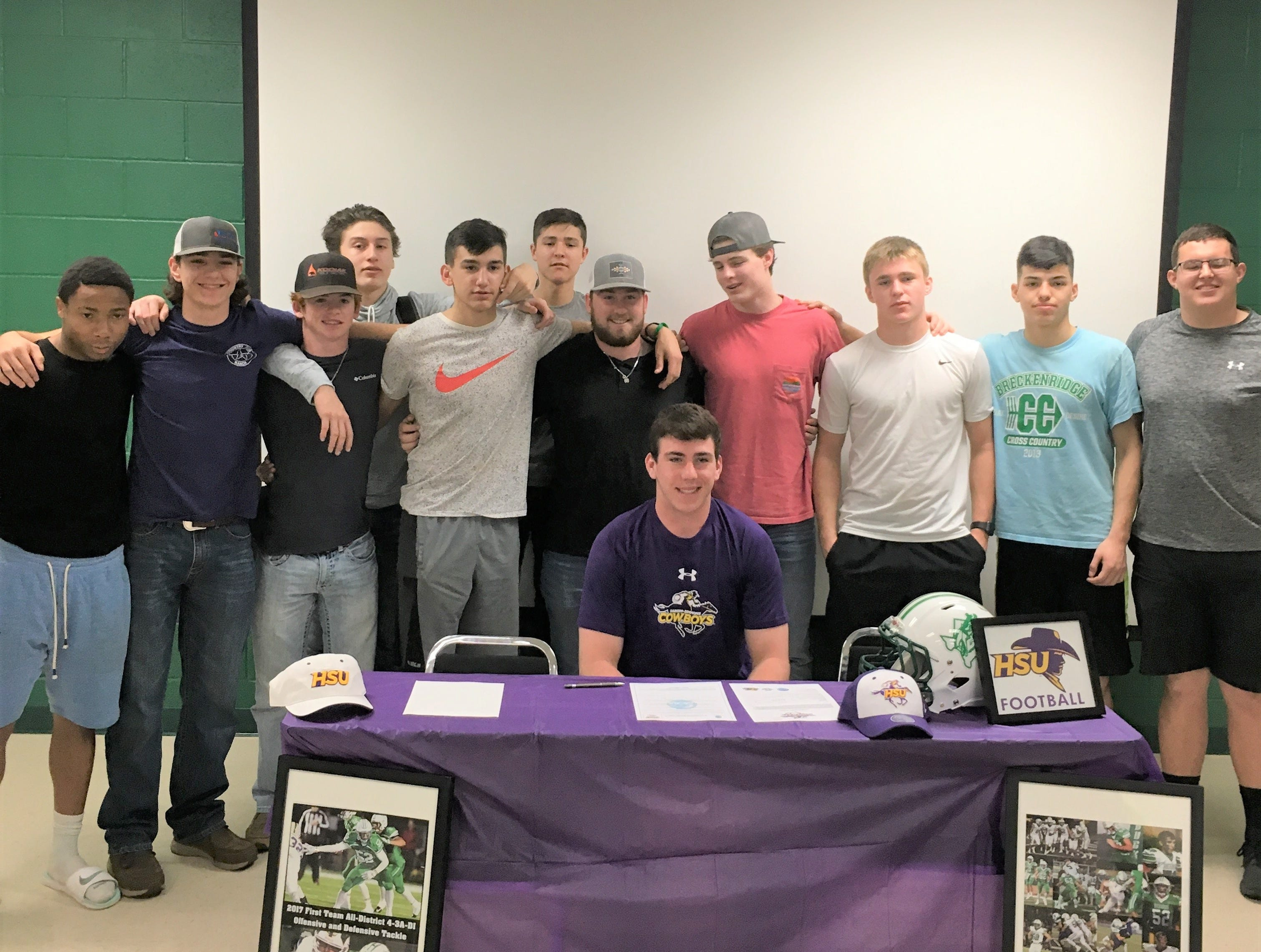 Breckenridge's Rance Russell, seated, poses with teammates after signing with Hardin-Simmons football.