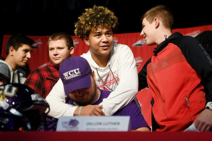 Erwin junior Mikey Gettman hugs Dillon Luther, who signed with Western Carolina University, during National Signing Day Wednesday, Feb. 6, 2019.