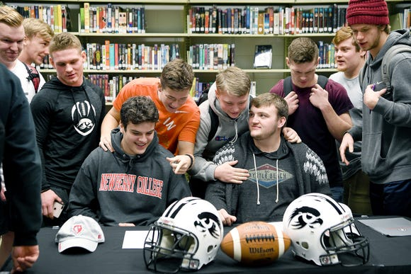 North Buncombe football players Spencer Harris, left, and Jackson Ramsey, right, are teased by teammates Caden Higgins, left, and Kolbie Hughey, right, as they gather for a group photo to celebrate Harris and Ramsey signing to play for Newberry College on Feb. 6, 2019.
