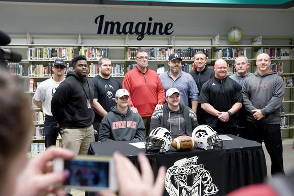 North Buncombe football players Spencer Harris, left, and Jackson Ramsey, right, pose with their coaches after signing to play for Newberry College on Feb. 6, 2019.