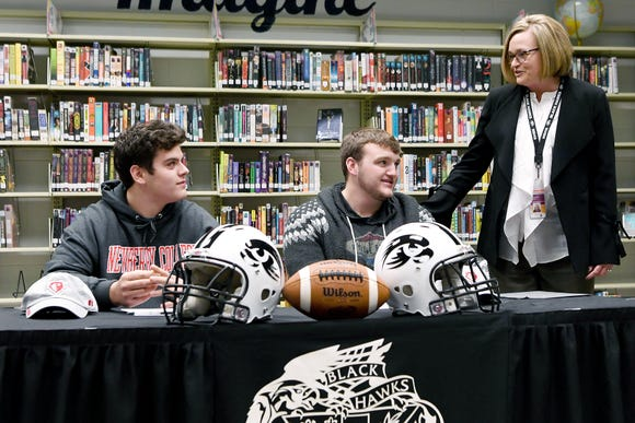 North Buncombe football players Spencer Harris, left, and Jackson Ramsey, right, are congratulated by North Buncombe principal Samantha Sircey before as they sign to play for Newberry College on Feb. 6, 2019.