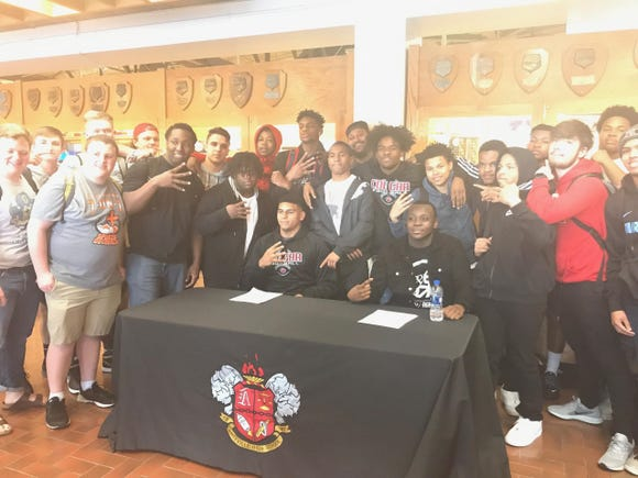 Asheville High's Marvin Pearson (left) signs with Elon and Keith Mosley (right) signs with Barton College
