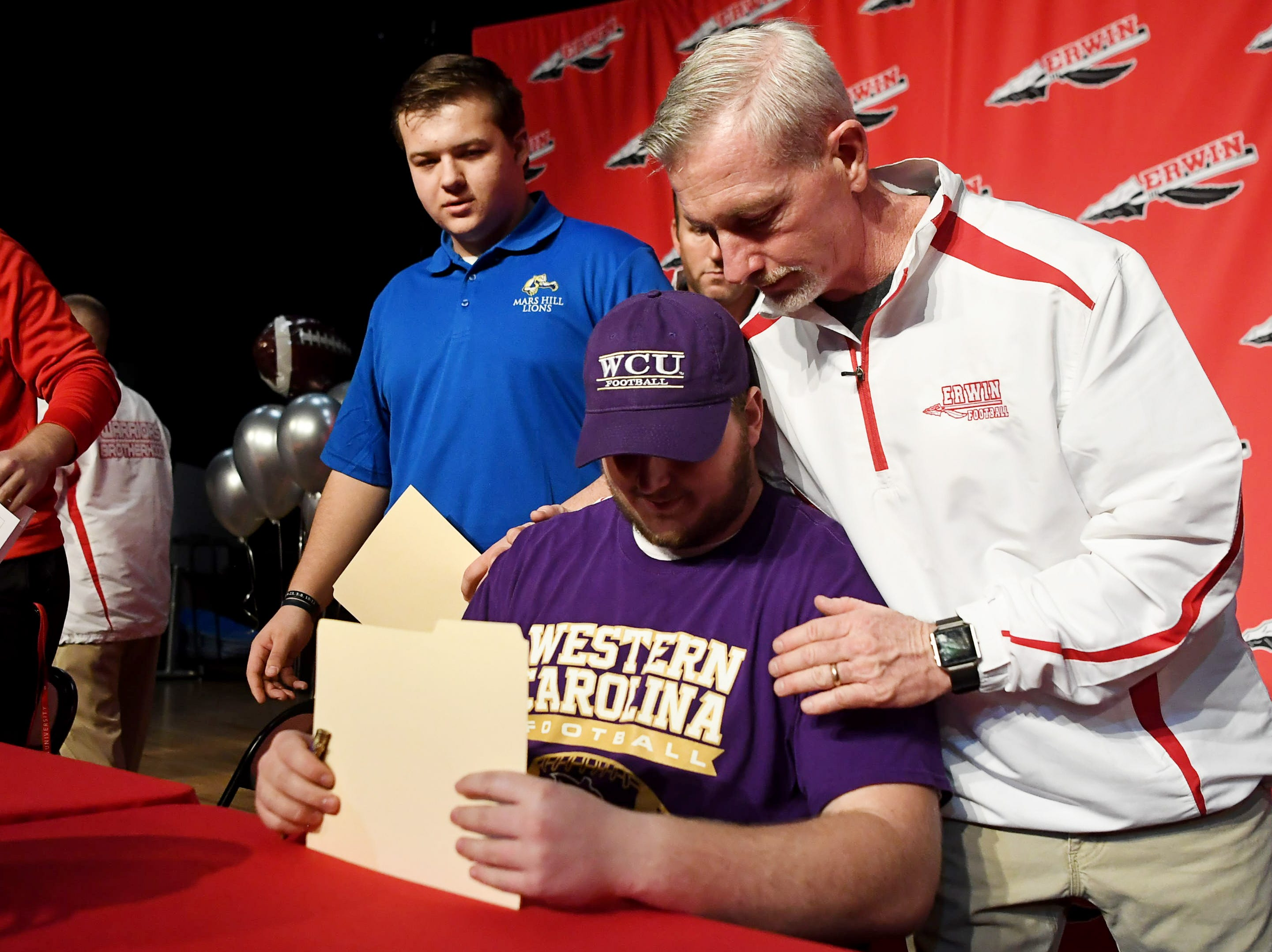 Erwin running back coach Patrick Bohanon hugs Dillon Luther after he signed to play football at Western Carolina University Feb. 6, 2019.