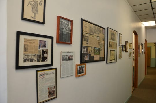 Hair Shed/Natural Woman owner Ken Bennett keeps a wall of old articles on his 51-year-old business.
