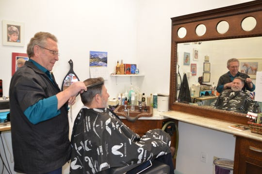 Ken Bennett (left) has been a barber downtown for more than 50 years, and Stan Horn has been a customer for nearly the entire time. Bennett will be retiring by the end of May.