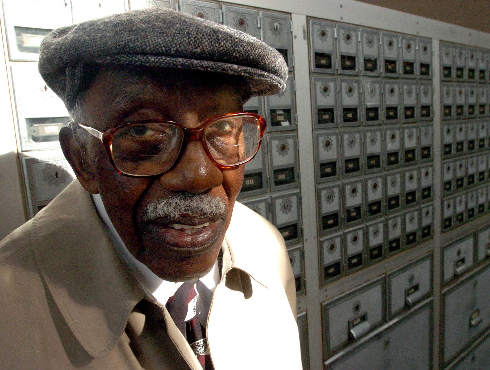 2006: William Delamar, 90, of Castle Creek, the first black postmaster general in Binghamton, stands in front of P.O. boxes ay the Henry Street post office Saturday in Binghamton.