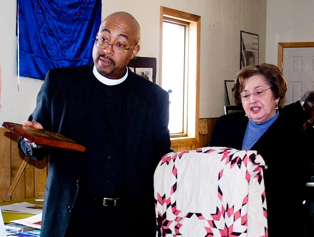 2007: Nellie Jennings of Elmira shows off a quilt her grandmother made for her 1881 wedding in Horseheads during a Black History Month event Sunday at the Frederick Douglass AME Zion Church in Elmira. At left is the Rev. Vincent Howell, the assistant church pastor who organized the event.
