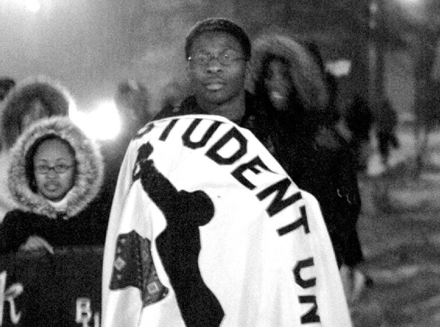 2005: Black Student Union historian Semande Agosa wraps himself with the BSU banner during a unity march in celebration of Black History Month at Binghamton University Thursday.