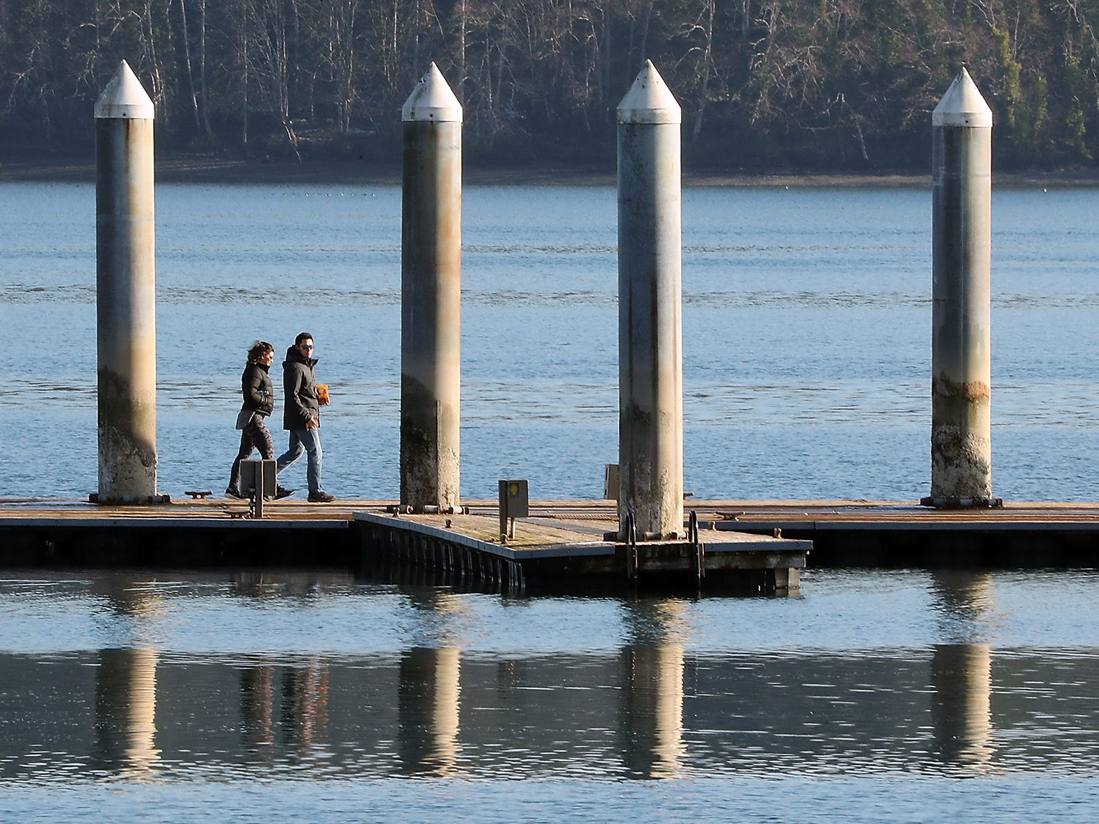 People walk along the pier at Silverdale Waterfront Park on a sunny yet chilly Wednesday, February 6, 2019.