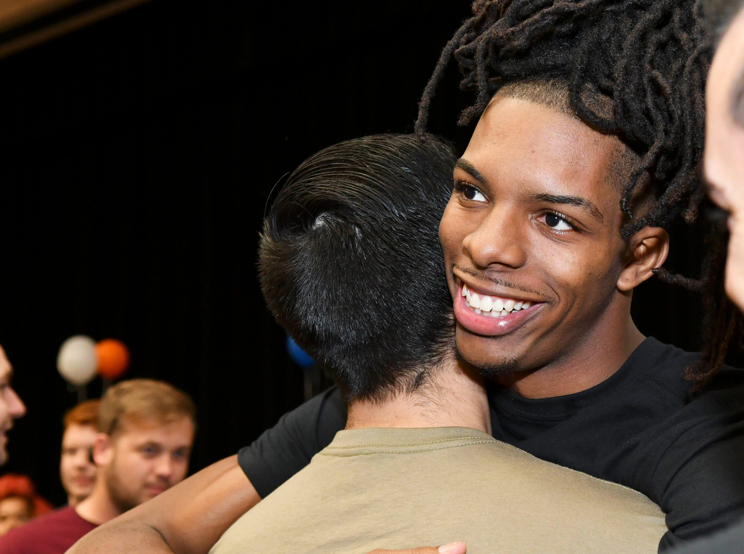 Rashean Lynn gets a congratulatory hug after signing his letter of intent on National Signing Day at Cocoa High School.  He will attend West Virginia.