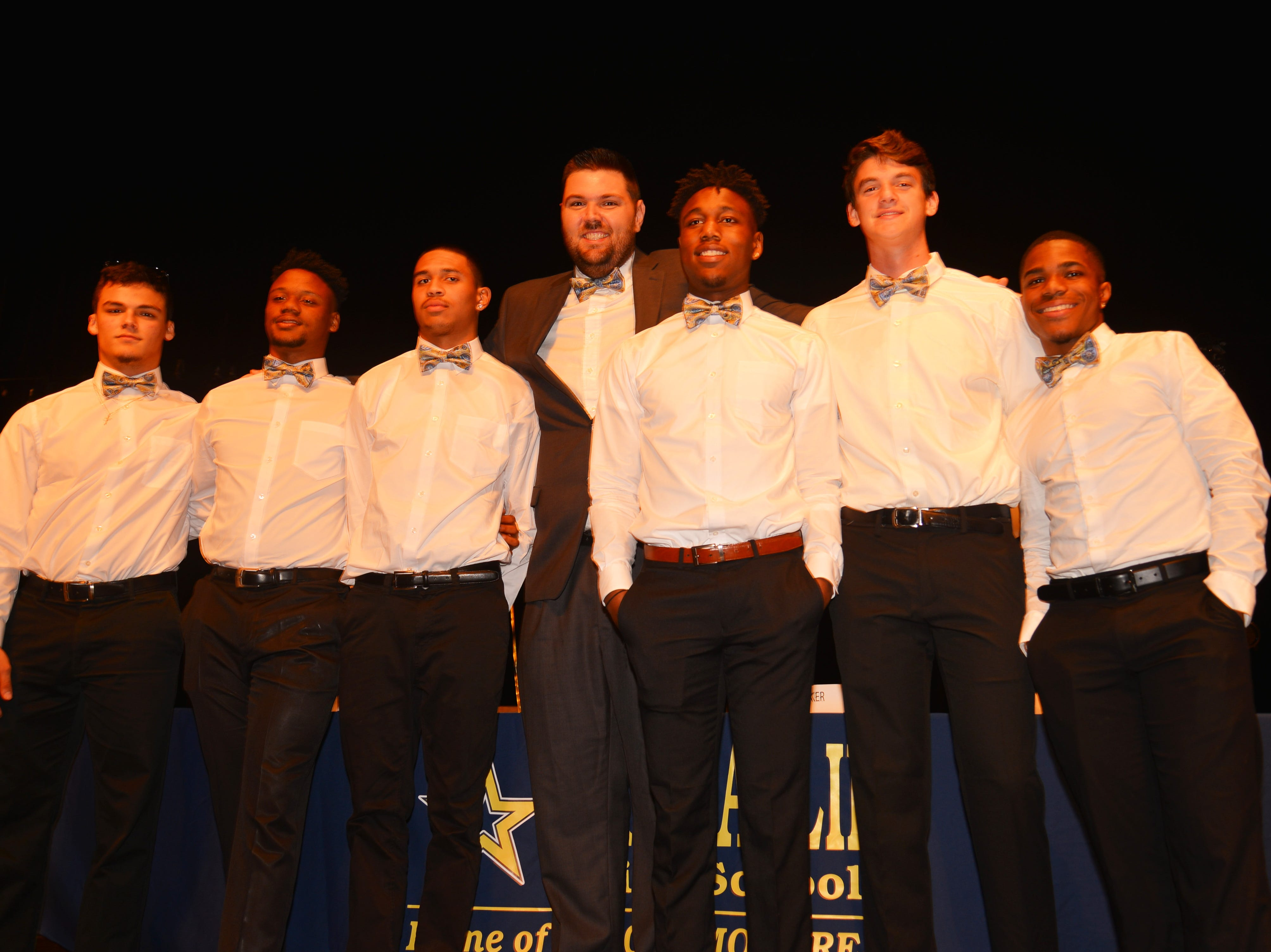 Eau Gallie High School had 11 athletes sign letters of intent on Wednesday. The he six plauyers who signed stand with their head coach Chris Sands.