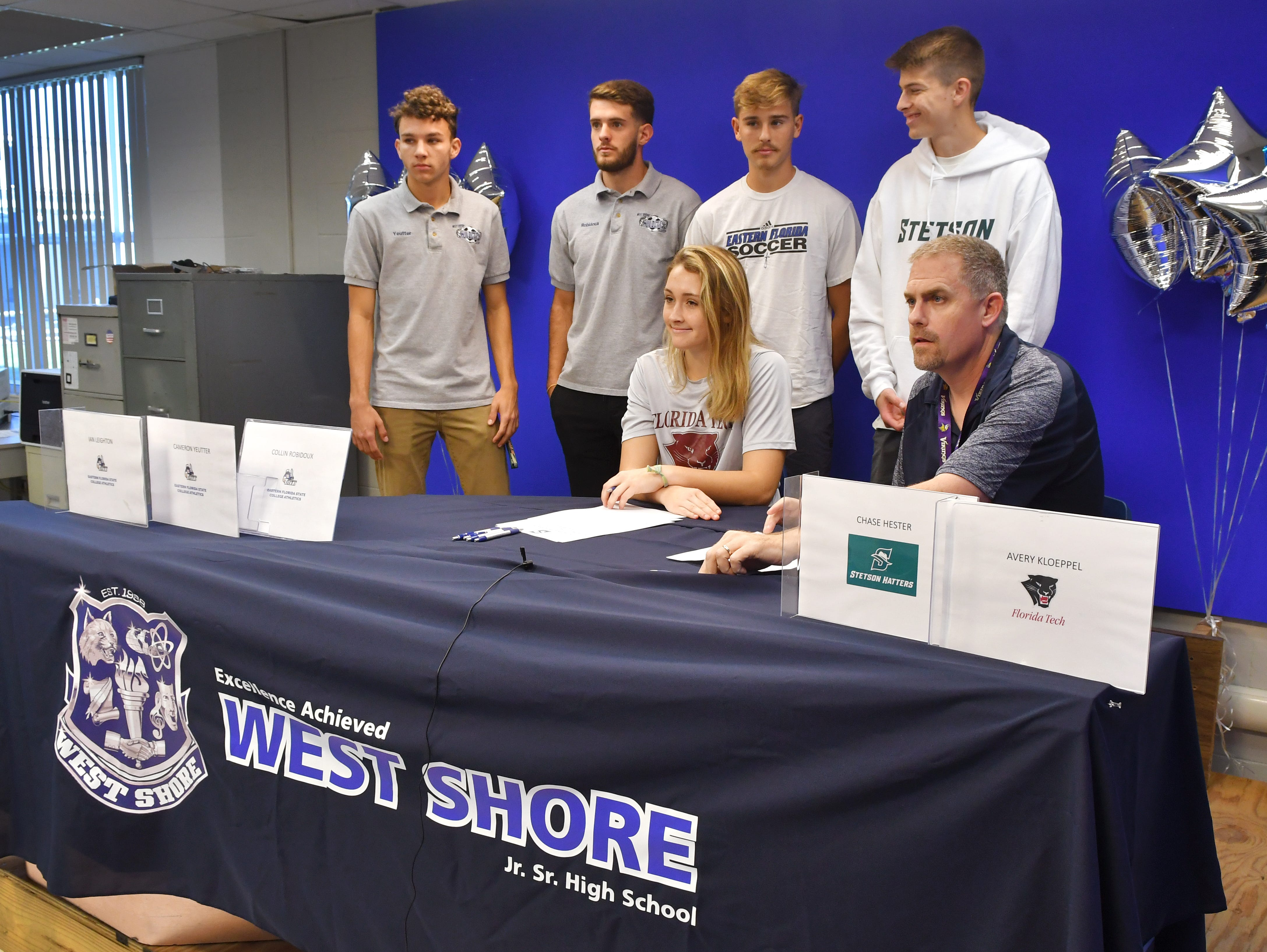 Five soccer athletes from West Shore Junior/Senior High School in Melbourne signed letters of intent on Wednesday. Seated is Avery Kloeppel, Florida Tech, with West Shore Athletic Director Tony Rioppelle. Standing, left to right, is Cameron Yeutter, Collin Robidoux and Ian Leighton, all for Eastern Florida State College, and Chase Hester, for Stetson University.
