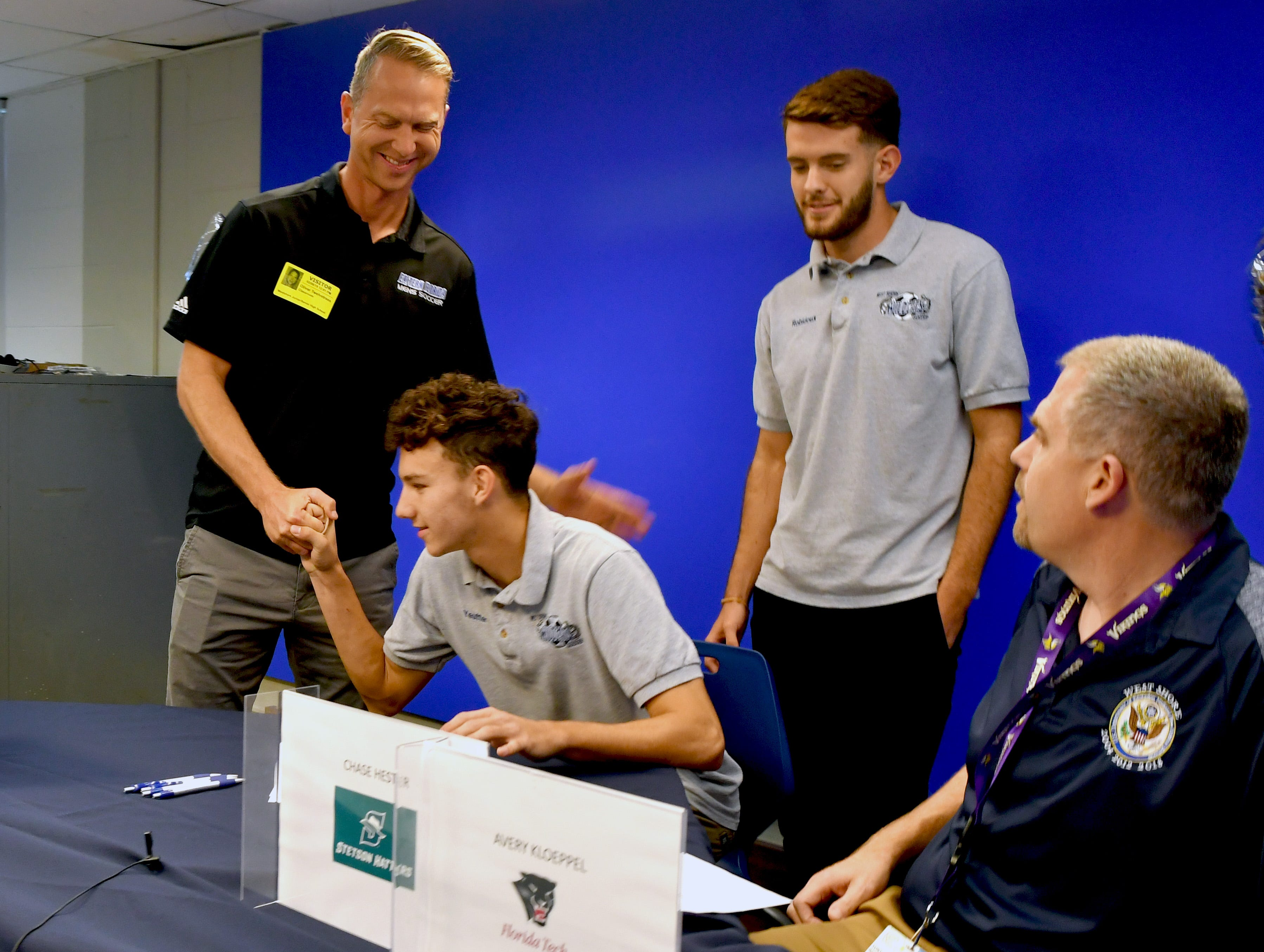 Oliver Twelvetrees of EFSC soccer shakes the hand  Cameron Yeutter, one of Five soccer athletes from West Shore Junior/Senior High School in Melbourne signed letters of intent on Wednesday.