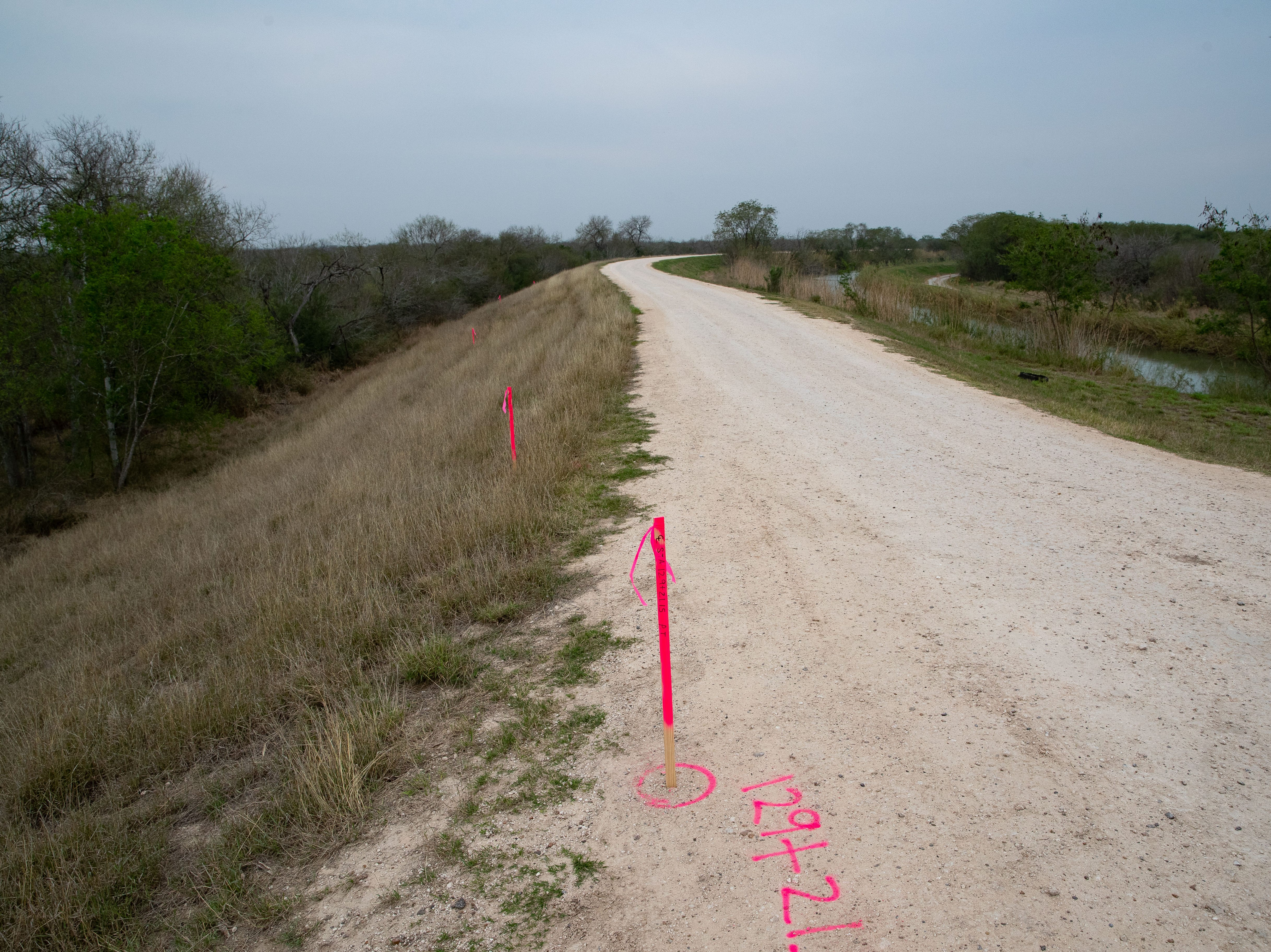 Markers for planned construction on fencing and other barriers line the side of a road in Mission, Texas.
