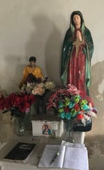 Statue of the Virgin Mary and handwritten expressions of faith inside La Lomita Chapel in Mission, Texas.