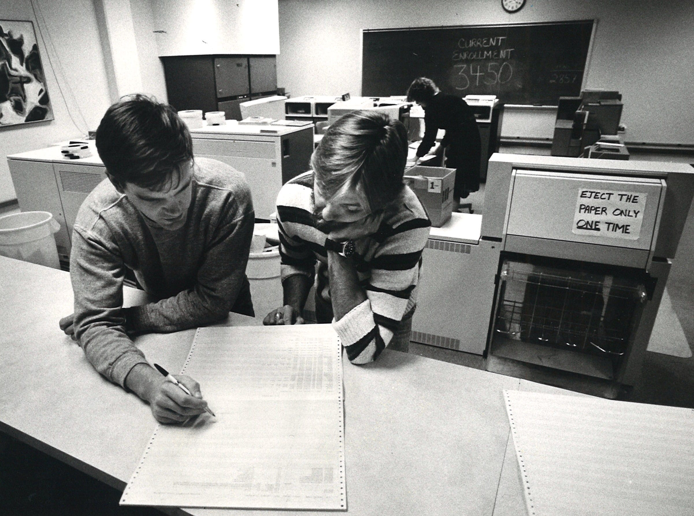 Stewart Hunt (left) and Jeff Grable (right), both graduate students in computer science at Corpus Christi State University, discuss a program designed by HUnt in the CCSU computer center in Corpus Christi Hall on April 7, 1983.