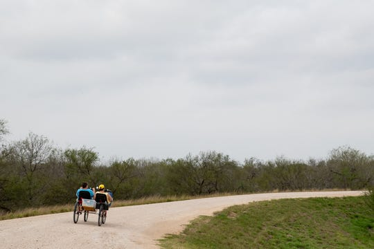 People ride a bike along the levee near the National Butterfly Center in Mission, Texas on Wednesday, Feb. 6, 2019. The center will have about 70 percent of its property cut off by the proposed border wall along the levee in the area.