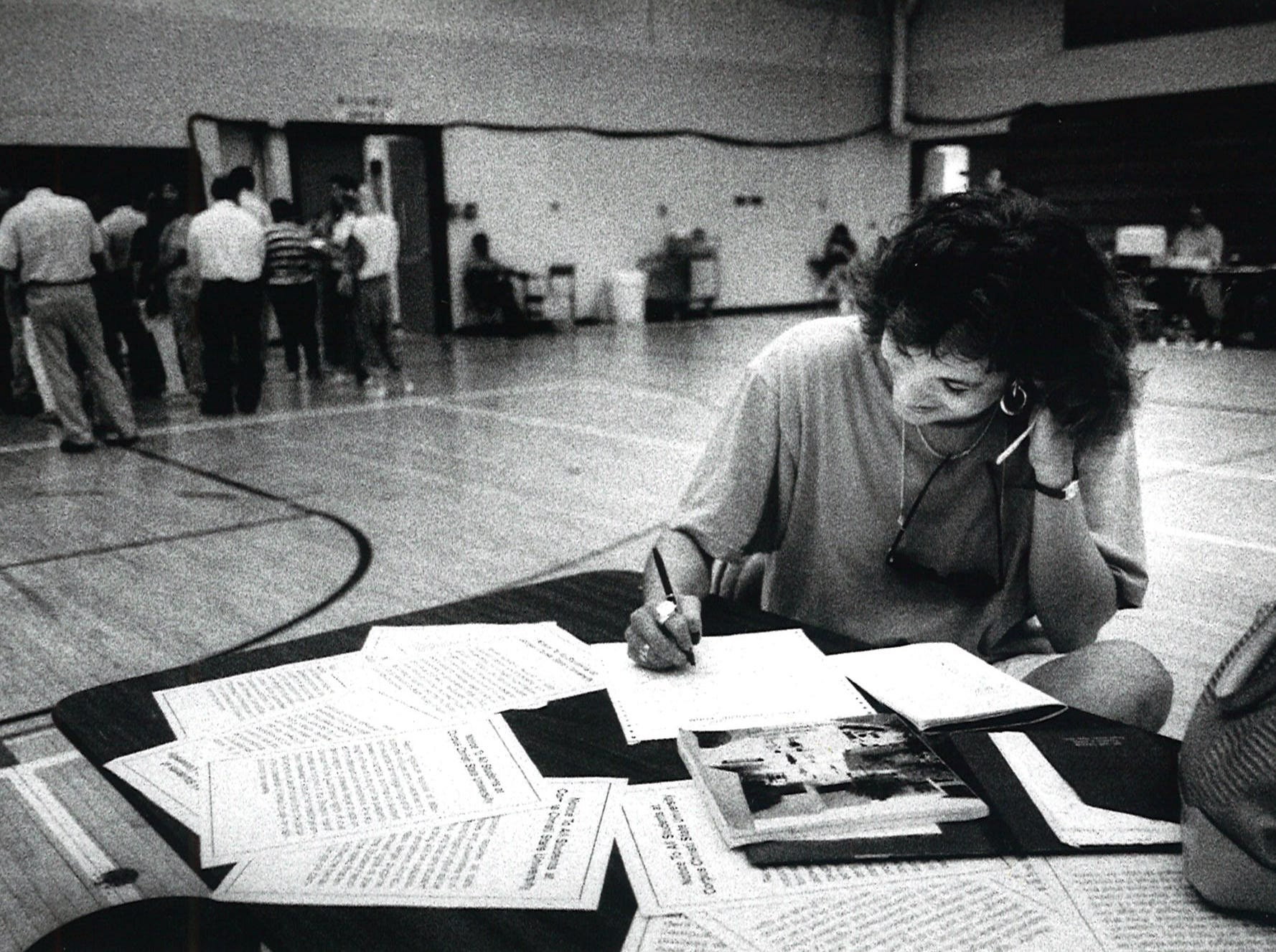 Belinda Flores of Orange Grove creates her class schedule while other students line up to pay their tuition and fees during summer school registration at Corpus Christi State University on May 31, 1990.