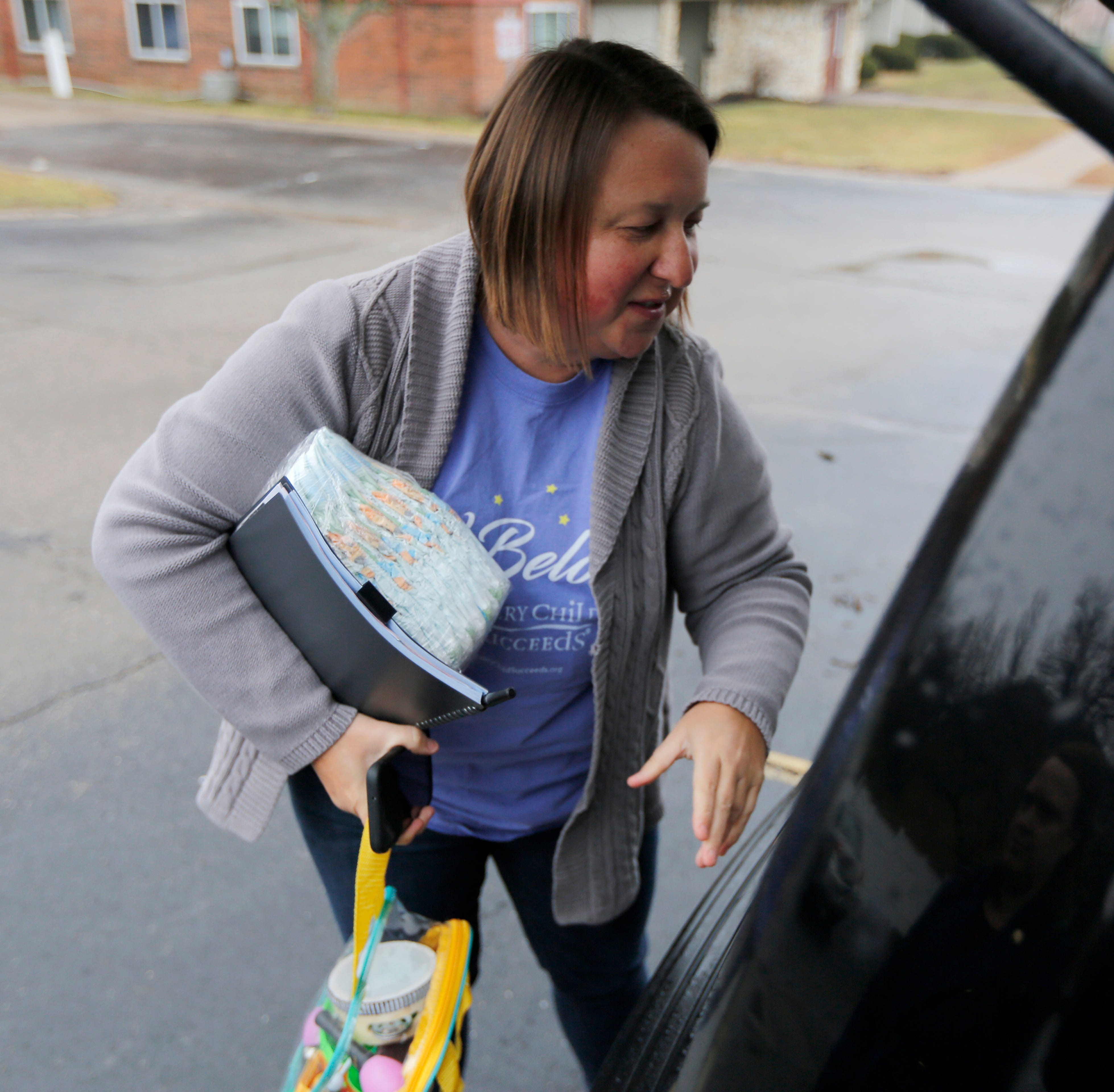 Every Child Succeeds supervisor Mindy Heathcoat Maurer packs up supplies and toys on a weekly visit to Ashley Ohmart, a young mother living in the Westwood neighborhood of Cincinnati on Tuesday, Feb. 5, 2019.