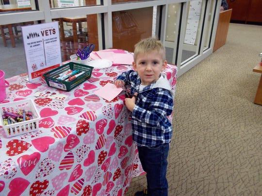 Brandon Campbell, 3, of Hillsborough, craftsa Valentine for a veteran.