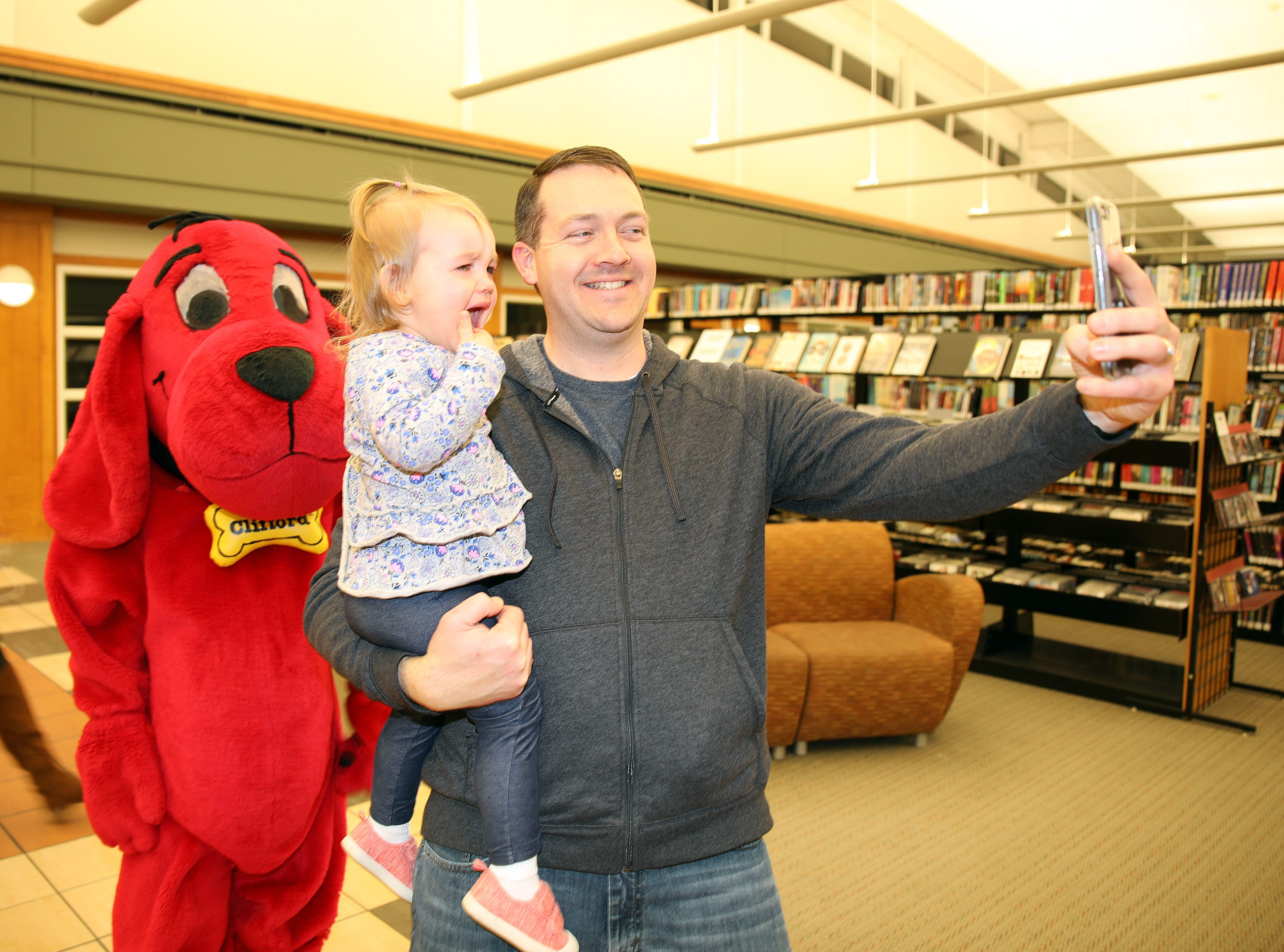 Andy Stearns of Ankeny snaps a quick selfie with his daughter, Abi, 2, and a Clifford the Big Red Dog during Clifford's birthday party at Kirkendall Public Library in Ankeny on Tuesday, Feb. 5, 2019.