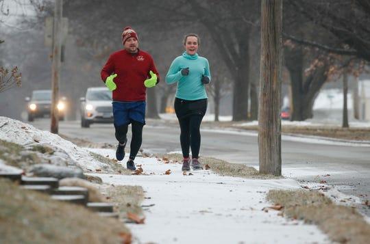 Jason Westholm and Melanie Mueller run along Urbandale Avenue in the Beaverdale neighborhood on Wednesday, Feb. 6, 2019.