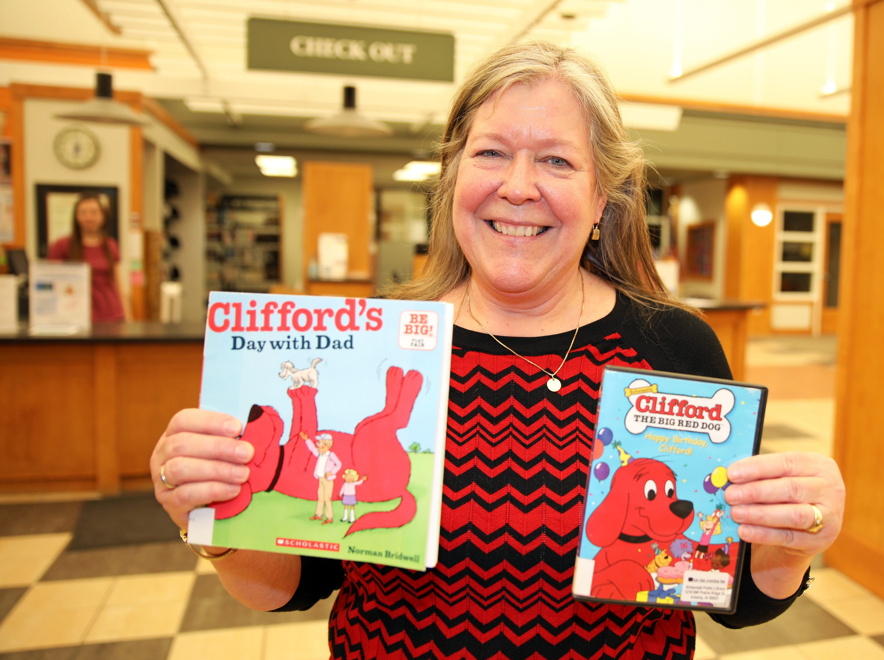 Youth and Children's Librarian Sherry Schlundt holds a few of the Clifford items available for checkout, during a birthday party for Clifford the Big Red Dog at Kirkendall Public Library in Ankeny on Tuesday, Feb. 5, 2019.