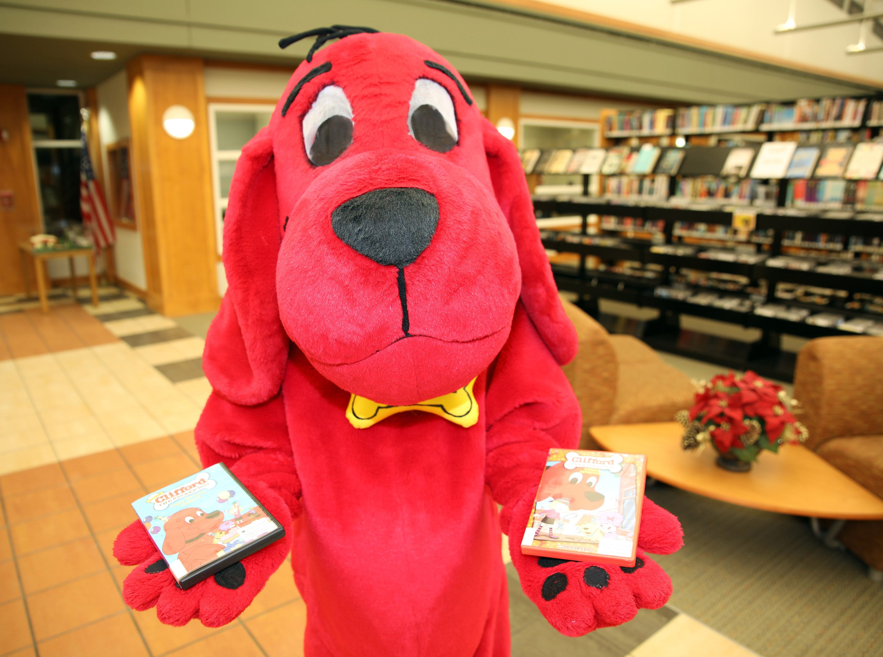 Clifford the Big Red Dog holds a few DVDs available to check out during his birthday party at Kirkendall Public Library on Tuesday, Feb. 5, 2019.
