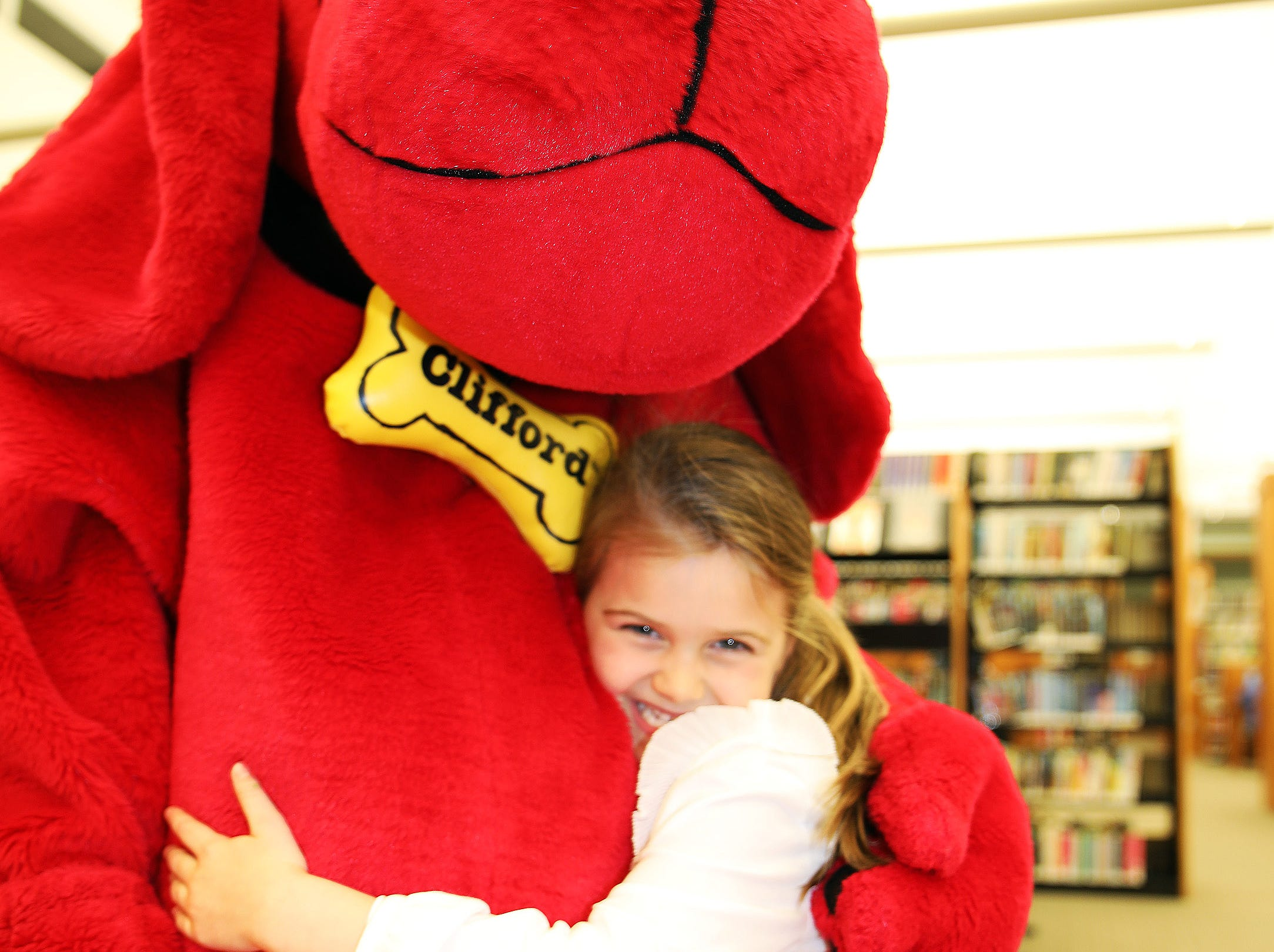 Adisyn Metzger, 5, of Ankeny receives a big hug from Clifford the Big Red Dog during his birthday party at Kirkendall Public Library in Ankeny on Tuesday, Feb. 5, 2019.