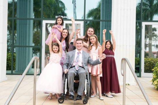 Native Iowa Chris Norton, seated, and his family celebrate adopting four little girls Feb. 4 in Florida.