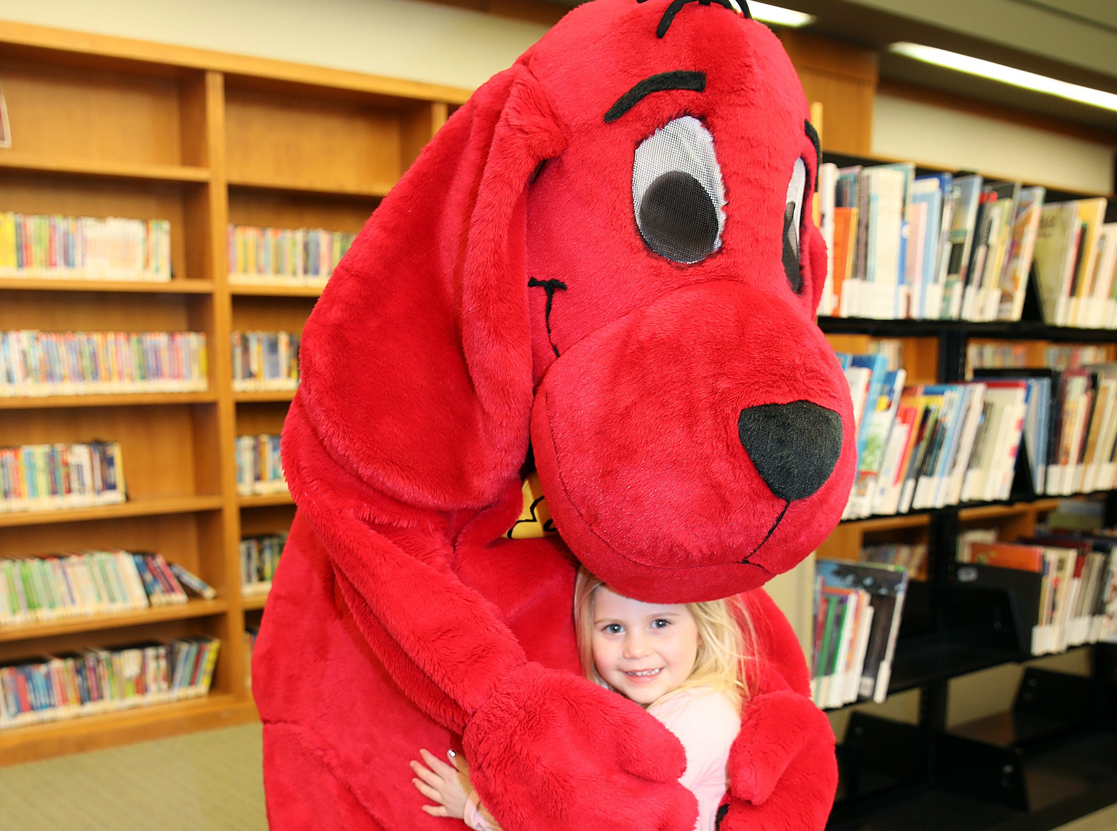 Clifford the Big Red Dog and Aubri Kucik, 3, of Ankeny hug during his birthday party at Kirkendall Public Library in Ankeny on Tuesday, Feb. 5, 2019.