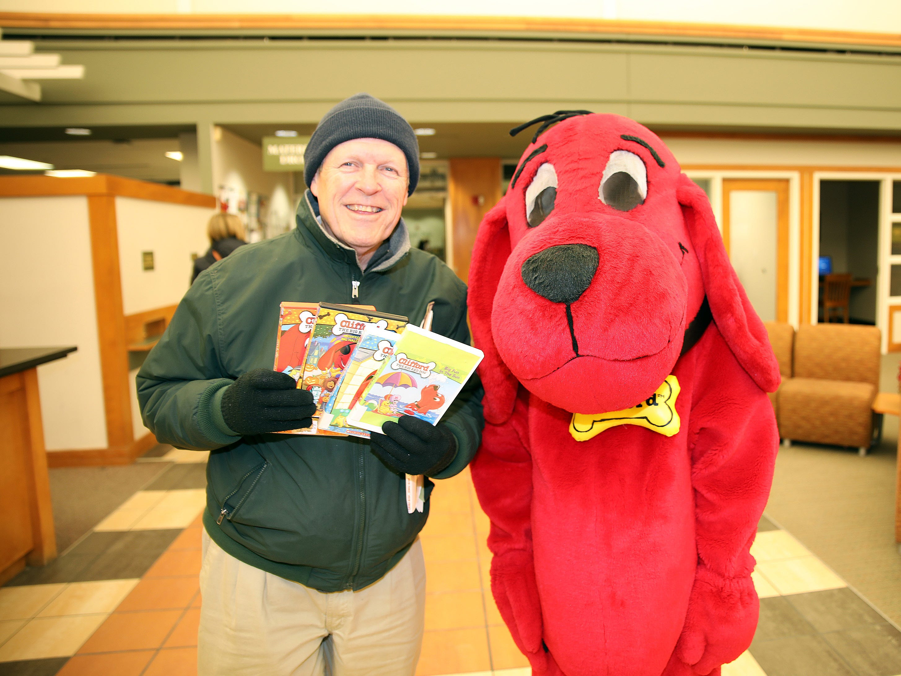 Long-time library patron Curt Bachman of Ankeny stops by to celebrate during a birthday party for Clifford the Big Red Dog at Kirkendall Public Library in Ankeny on Tuesday, Feb. 5, 2019.