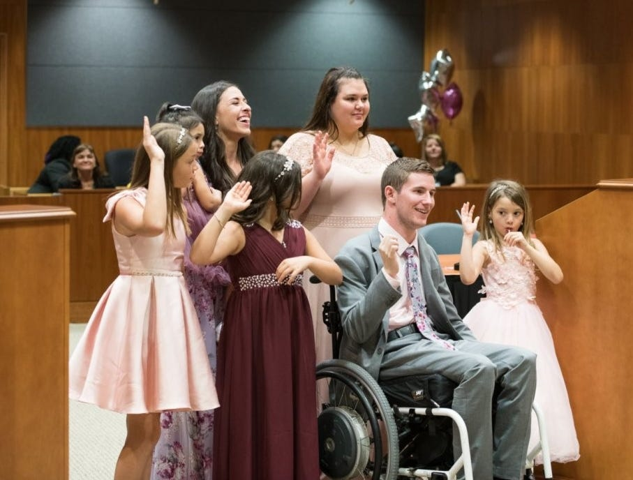 Iowan Chris Norton, sitting, celebrates adopting four girls at a Florida courthouse Feb. 2.