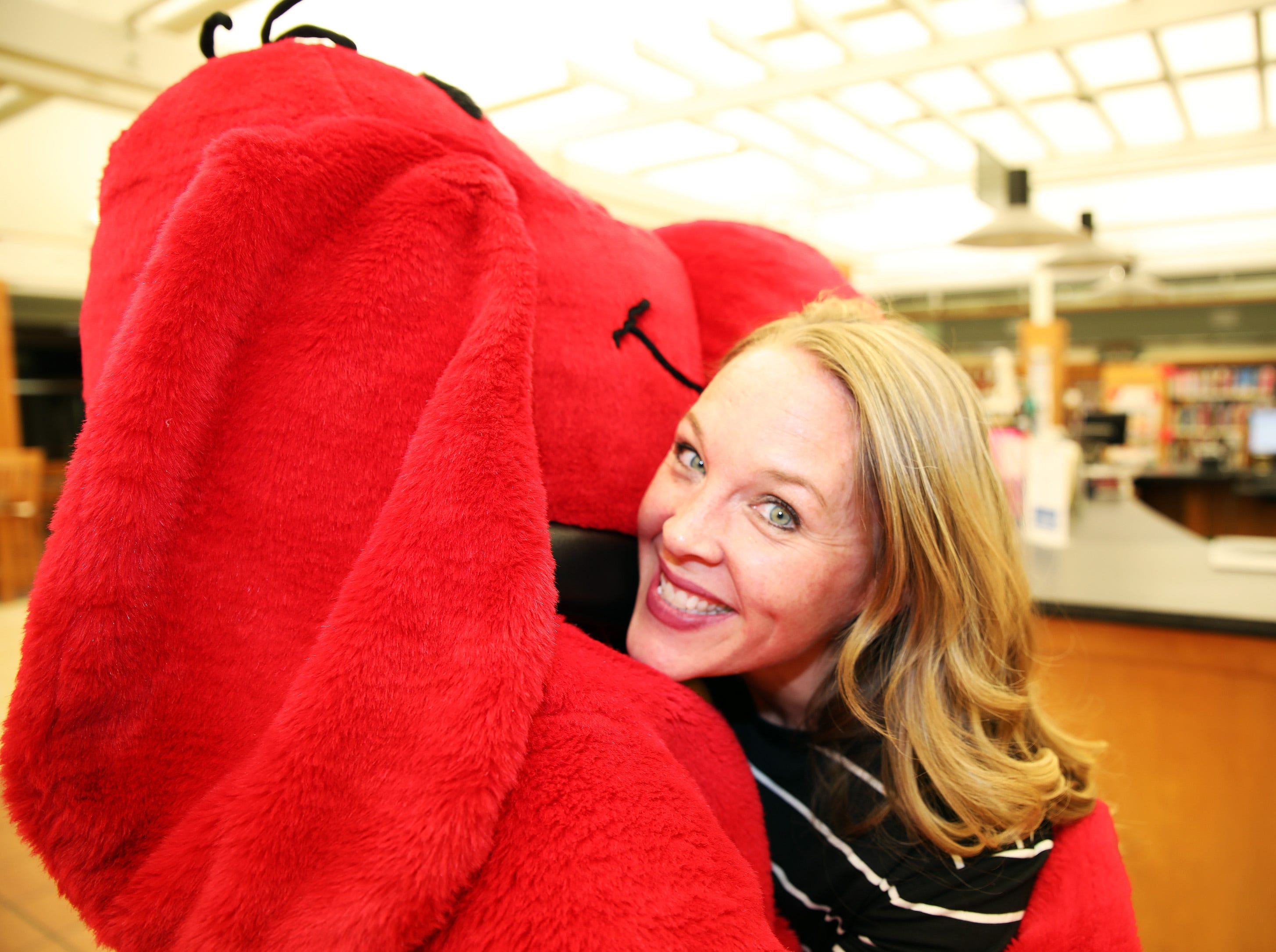 Children's Librarian Kelly Munter receives a big hug from Clifford the Big Red Dog during his birthday party at Kirkendall Public Library in Ankeny on Tuesday, Feb. 5, 2019. The long-running series of books about Clifford began in 1963 by author Norman Bridwell.