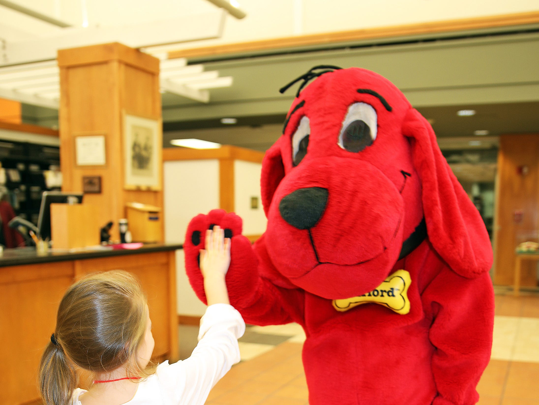 Clifford the Big Red Dog gives Adisyn Metzger, 5, of Ankeny a high-five during his birthday party at Kirkendall Public Library in Ankeny on Tuesday, Feb. 5, 2019.