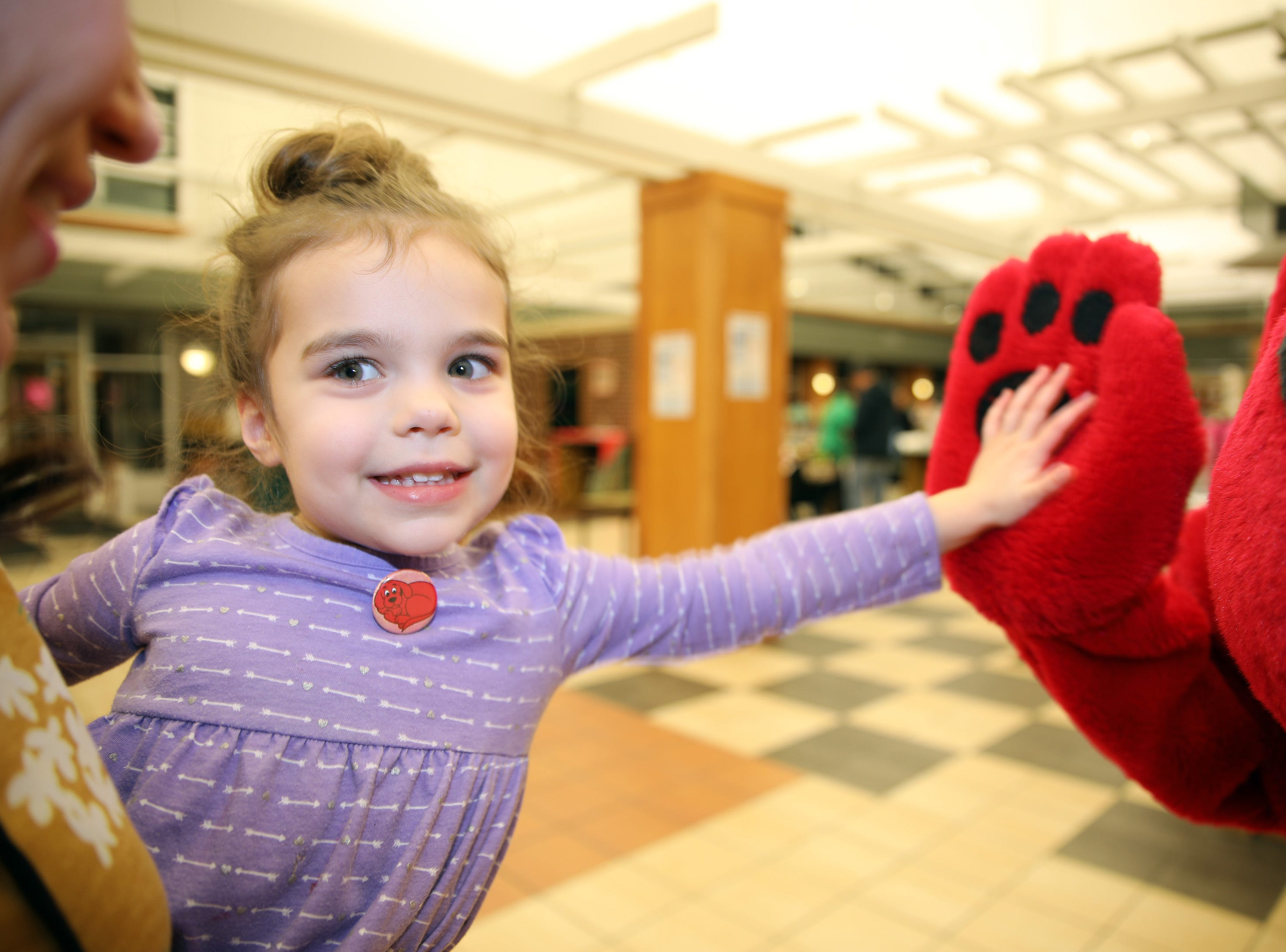 Lilly Marusiak, 3, of Ankeny gets a high-five from Clifford the Big Red Dog during his birthday party at Kirkendall Public Library in Ankeny on Tuesday, Feb. 5, 2019.