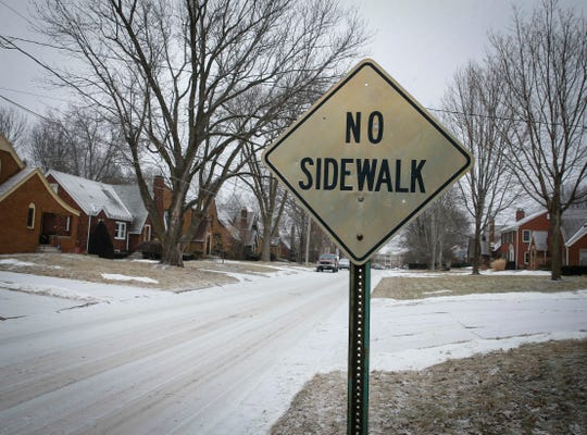 A sign informs there are no sidewalks on a street in the Beaverdale neighborhood on Tuesday, Feb. 6, 2019.