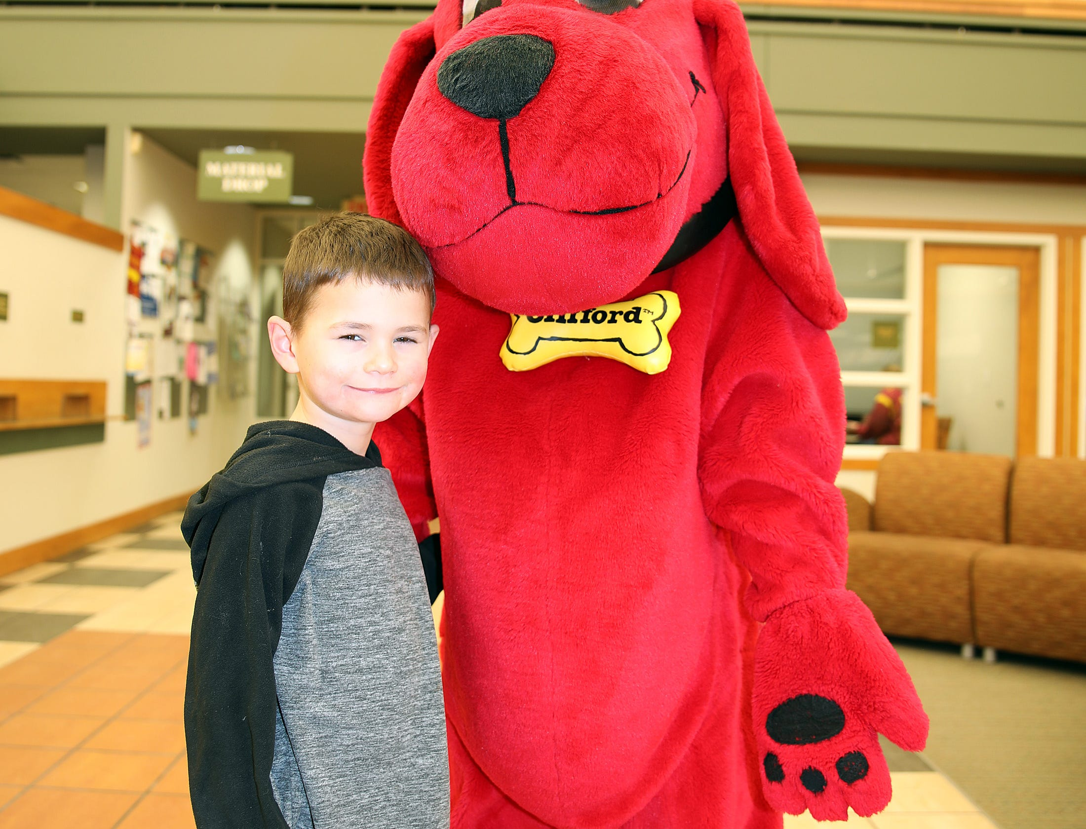 Max Brower, 6, of Ankeny stops for a photo with Clifford the Big Red Dog during Clifford's birthday party at Kirkendall Public Library in Ankeny on Tuesday, Feb. 5, 2019.