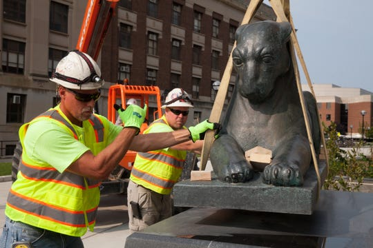 The museum's iconic pumas are lifted and moved to their new guard post outside the museum's new main entrance.