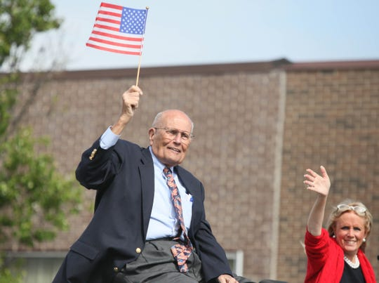 John Dingell smiles with his wife while riding in the Memorial Day parade in Dearborn, Michigan, on May 27, 2013.