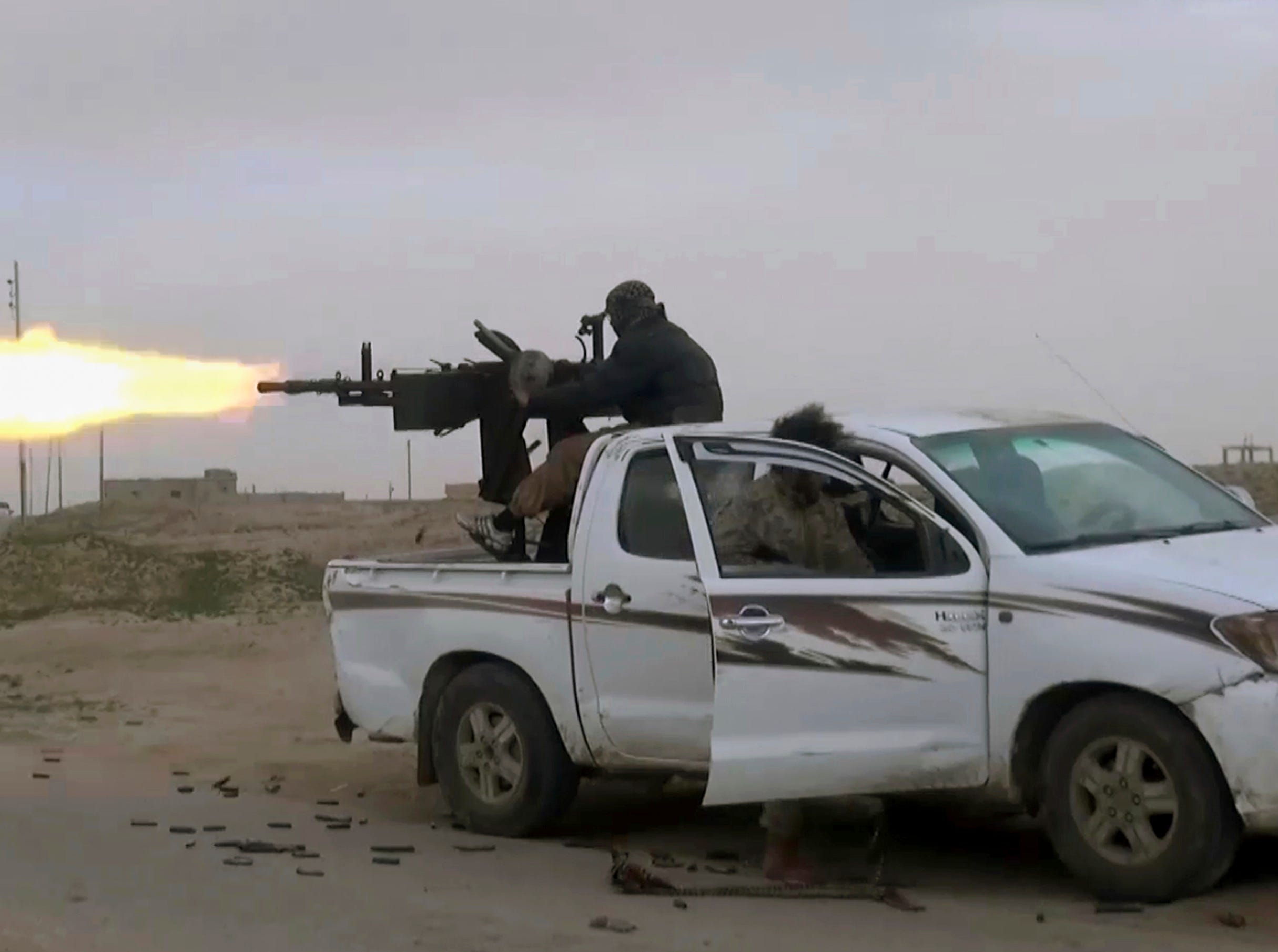 This frame grab from video posted online Friday, Jan. 18, 2019, by supporters of the Islamic State group, purports to show a gun-mounted Islamic State group vehicle firing at members of the U.S.-backed Syrian Democratic Forces, in Deir el-Zour, Syria.