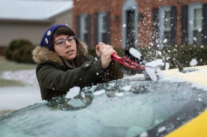 Lucy Sobel scrapes the ice from her car at her Farmington Hills home on Wednesday, Feb. 6, 2019, after a freezing rainstorm moved through the area.
