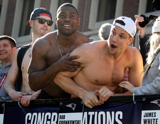 Patriots tight ends Dwayne Allen, left, and Rob Gronkowski react to fans during their victory parade Tuesday.